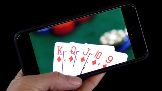 Hand hält ein Smartphone mit einem Kartenset drarauf.