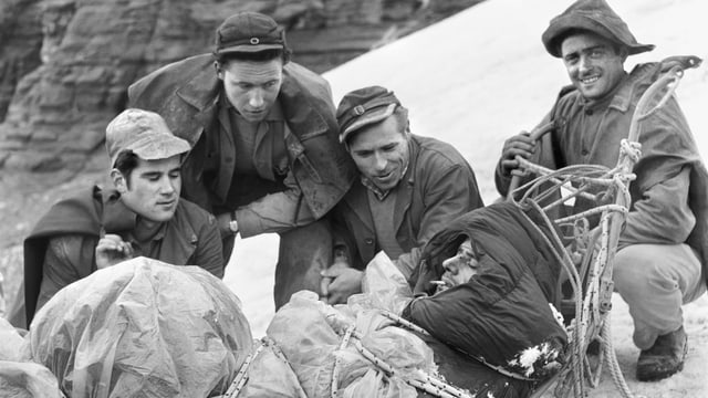 Schwarzweissfoto: Vier Männer knien neben einem Rettungsschlitten, auf dem ein weiterer, dick eingepackter Mann liegt. Einer der Männer schaut lächelnd in die Kamera
