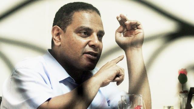 Alaa al-Aswani raucht. Ein verschwungener linienförmiger Schatten legt sich über ihn.
