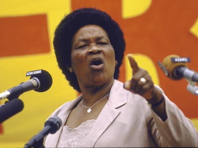 Eine Frau steht mit erhobenen Zeigefinder am Mikrofon.