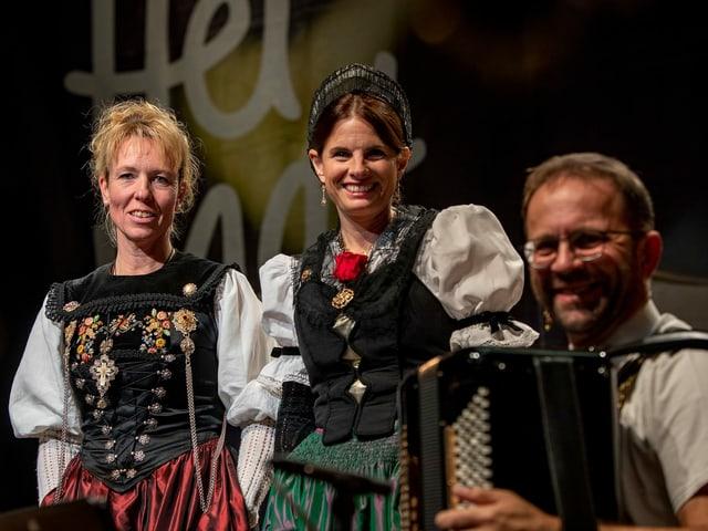 Zwei Trachtenfrauen und ein Akkordeonist.