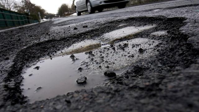 Ein mit Wasser gefülltes Schlagloch in einer Strasse. Im Hintergrund ist ein Auto erkennbar.
