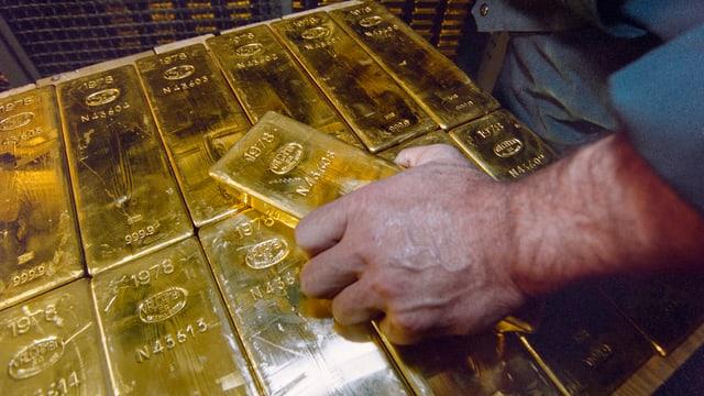 Viele Goldbarren sind in einer Kiste. Ein Mann hält einen Goldbarren in der Hand