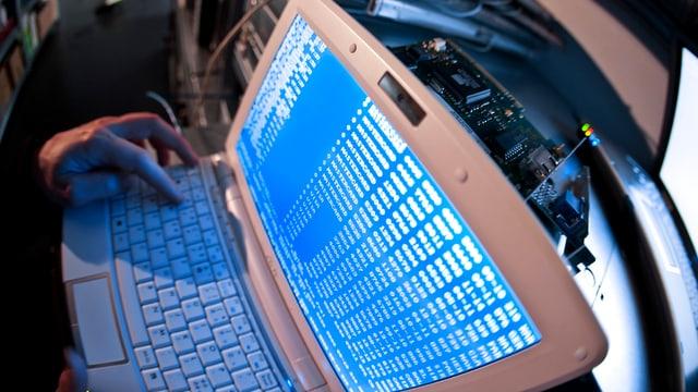 Computer mit blauem Bildschirm, Hand auf Tastatur.