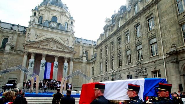 Im Vordergrund Polizisten, die einen Sarg mit Frankreich-Flagge tragen, dahinter die Treppe zum Pantheon, wo 4 Portraits an den Säulen hängen.