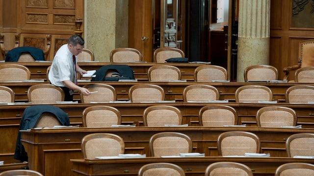 Ein Ratsweibel verteilt Papiere im Nationalratssaal vor der Session der Eidgenoessischen Räte
