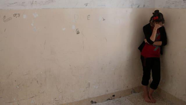 Eine Frau steht in der Ecke eines leeren Raumes.