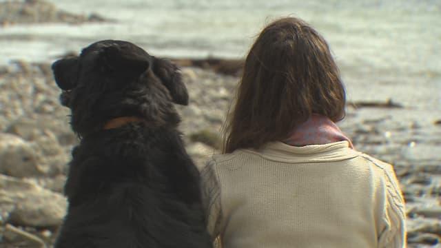Frau und Hund von hinten, am See sitzend