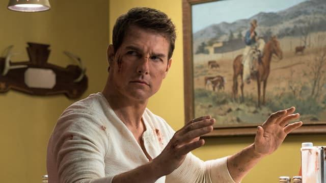 Tom Cruise alia Jack Reacher hebt die Hände hoch