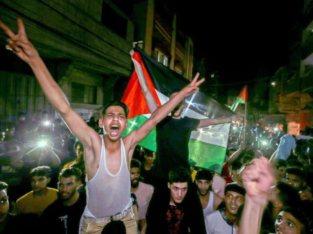 Ausgelassene Menschenmenge feiert und hält Palästina-Flaggen hoch