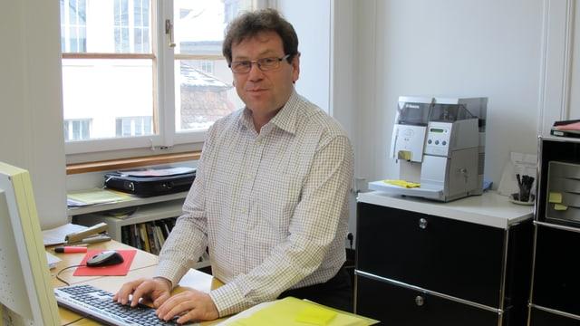 Peter Käppler mit braunen Haaren, Brille und schwarz-weiss kariertem Hemd am Stehtisch.