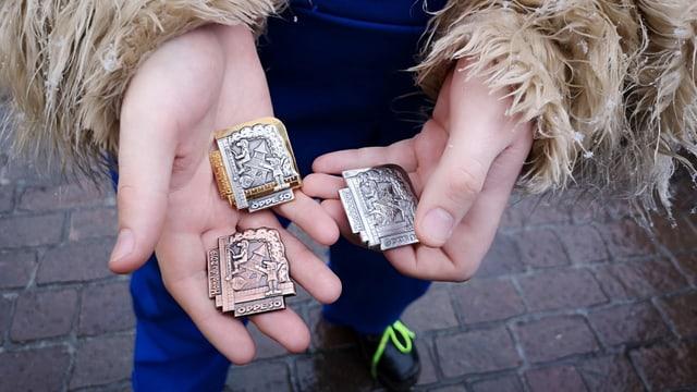 Drei Plaketten in Händen.