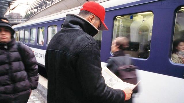 Ein wartender Fahrgast liest auf einem Perron des Bahnhofs in Uster eine Zeitung. (keystone)