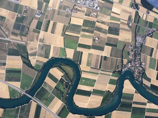 Flugbild auf das Schweizer Mittelland. Felder und Wiesen sind schachbrettartig angeordnet. Die Aare schlängelt sich als blauer Schlauch durch die Landschaft. Die Felder sind braun und sehr hell.