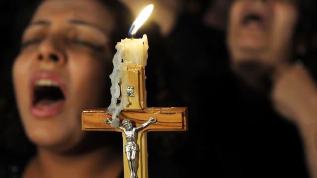 Singende koptische Christen halten ein Kreuz in der Hand.