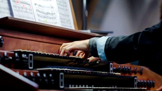 Ein Organist und ein mit Zetteln beklebtes Notenblatt.