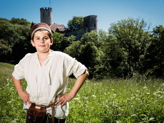Junge in mittelalterlicher Kleidung auf einer Wiese mit einer Burg im Hintergrund