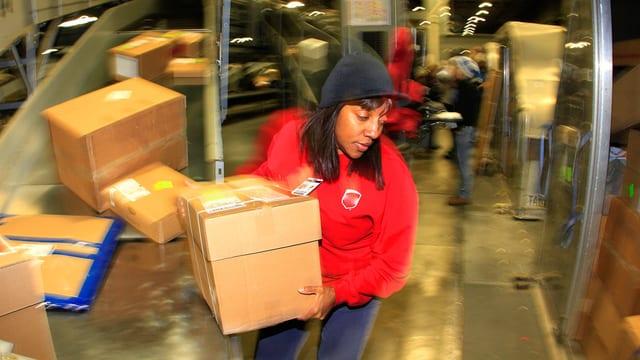 Eine Frau lagert in einem Paketdienst Pakete um.