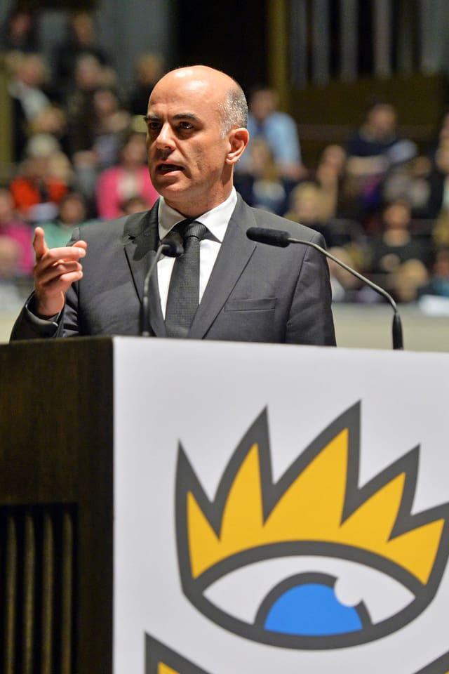 Ein Mann in dunklem Anzug steht an einem Pult und hält eine Rede.