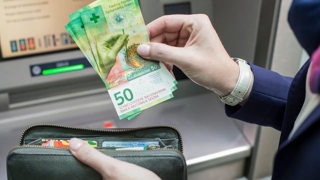 Frau hebt neue Note am Bankomat ab.