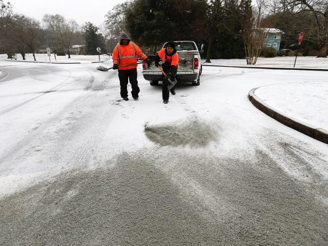Zwei Strassenarbeiter verteilen Streu auf den verschneiten Strassen.