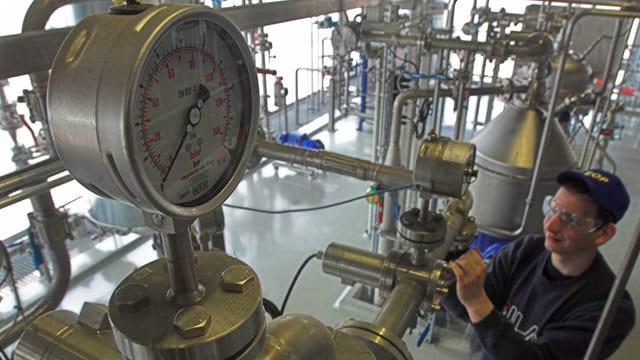 Arbeiter einer Biodieselfabrik bedient ein Ventil.