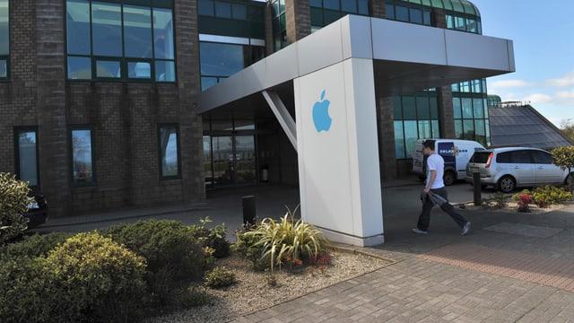 Ein Mann geht in ein Unternehmensgebäude von Apple in Irland.