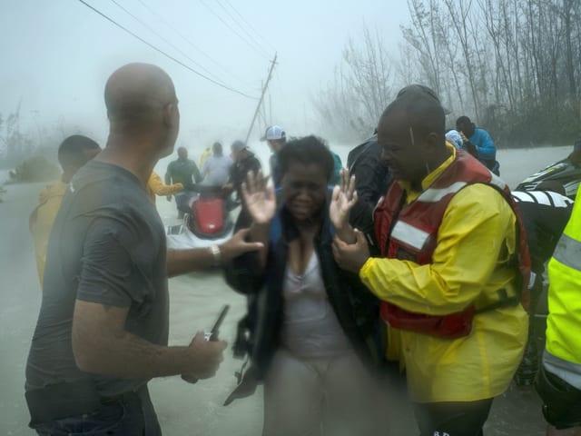 Frau wird bei Überschwemmung und Regen von Helfern begleitet.