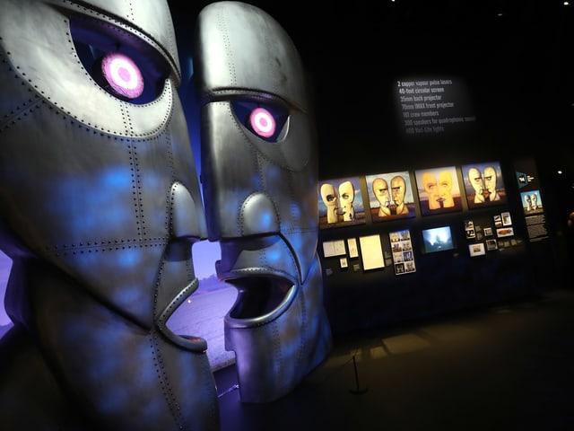 Im Museum: Zwei übergrosse Metallkopf-Skulpturen schauen einander an.