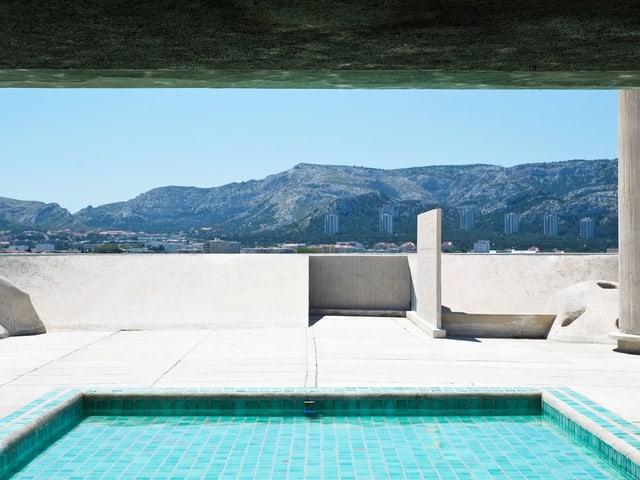 Pool bei modernem Betongebäude, im Hintergrund Hügelzug