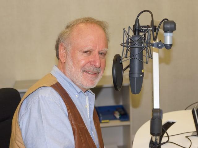 Mann sitzt im Radiostudio am Microfon.