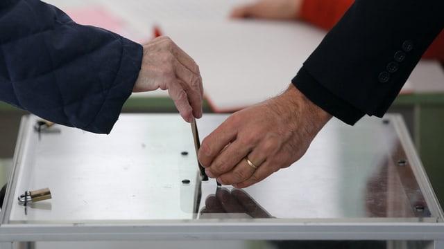 Insatgi che metta la cuverta da votar en l'urna.