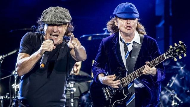 Purtret da Brian Johnson ed Angus Young da la band AC/DC durant in concert.