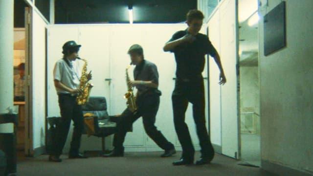Blick auf zwei Jugendliche auf einer Bühne, die nach hinten gebeugt Saxophon spielen, dahinter ein begeistert zuhörendes Publikum