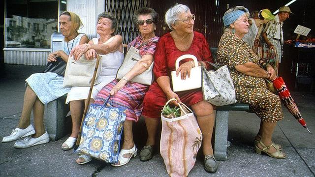 Ältere Damen sitzen auf einer Bank.