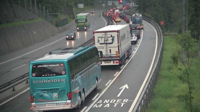 Stau vor dem Gotthardtunnel. Man sieht vorne im Bild einen grünlichen Car und einen weisslichen Lastwagen. Vor ihnen stauen sich mehrere Autos. Es ist bewölkt, die Fahrbahn nass.