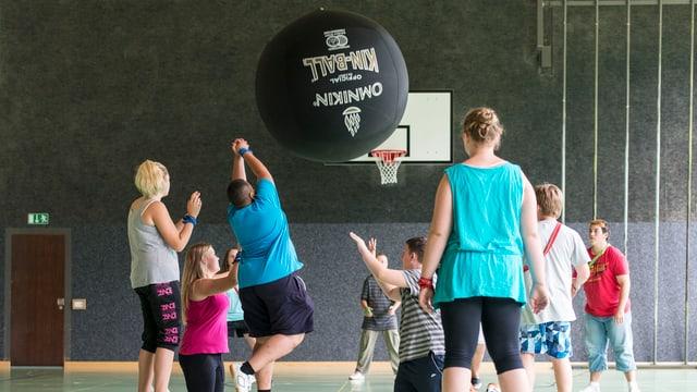 Übergewichtige Jugendliche treiben in der Turnhalle Sport.