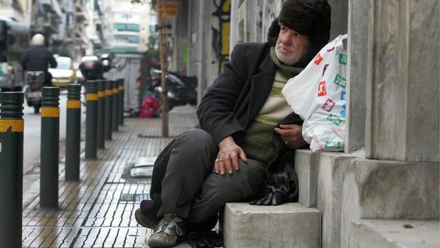 Ein Obdachloser sitzt in einem Hauseingeng.