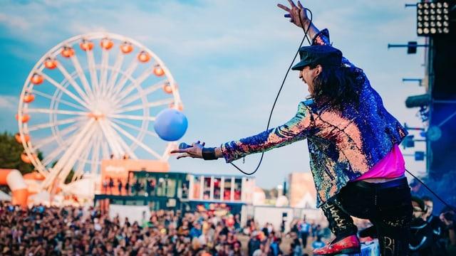 Ein Bandfrontman auf einer Bühne. Im Hintergrund
