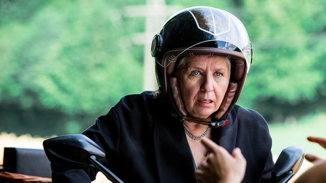 Bürgisser mit Helm auf einem Motorroller