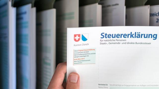 Eine Hand hält eine Steuererklärung des Kantons Zürich.