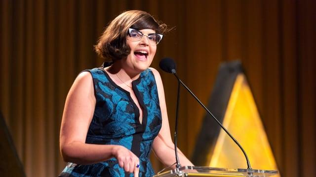 Eine junge Frau mit Brille an einem Rednerpult.