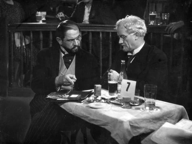 Zwei ältere Männer sitzen an einem Tisch in einem Restaurant. Auf dem Tisch liegt eine Aktenmappe. Der linke Mann zeigt mit dem Finger auf die Mappe.