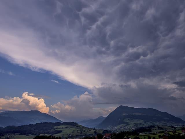 Landschaft mit Bergen. Am Himmel von rechts dunkle Wolken, links noch blau und sonnig.