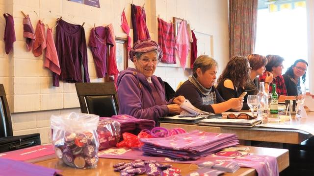 Eine Gruppe von Frauen, die an einem Tisch sitzen. Vor sich lilafarbene Anstecker und Prospekte