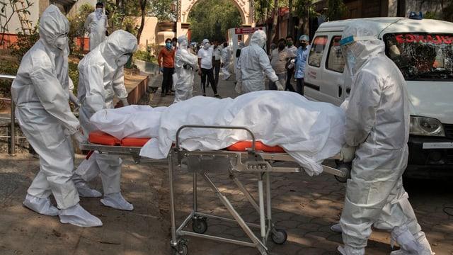 Krankentransport einer Leiche, alle Helfer in weisser Schutzkleidung.