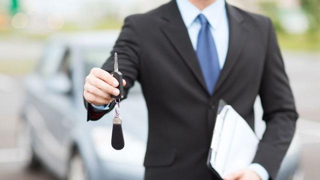 Ein Mann in Anzug steht vor einem Auto und überreicht einen Schlüssel