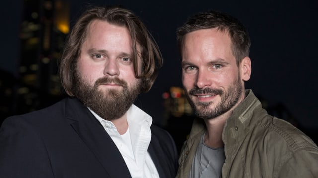 Zwei Männer blicken in die Kammera.