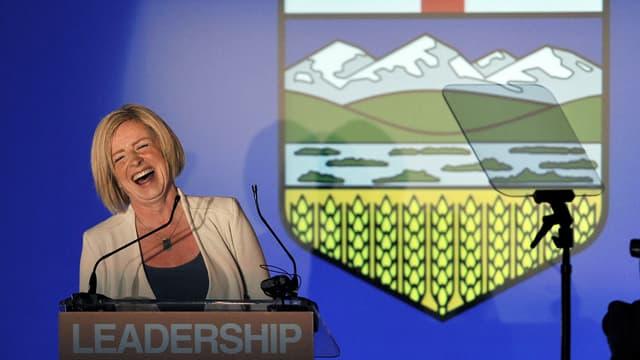 Eine Frau hinter einem Rednerpult lacht.