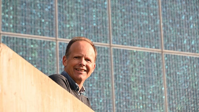 Ein Mann steht vor Solarpanelen.